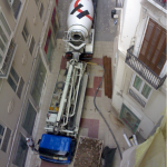 Bombeo de hormigón con tubería en muros de ascensor para la rehabilitación de un edificio en una quinta planta con autobomba estática.